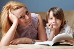 La madre joven con su hijo leyó el libro en el sofá Fotos de archivo
