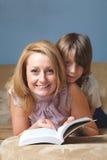 La madre joven con su hijo leyó el libro en el sofá Fotografía de archivo