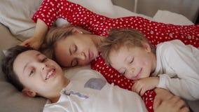 La madre joven con sus 2 hijos vestidos en pijamas es de relajación y que juega en la cama al fin de semana junto, perezoso metrajes