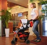 La madre joven con un carro de bebé rueda en la casa Imágenes de archivo libres de regalías
