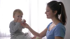 La madre joven da el pequeño vidrio del hijo de agua mineral para apagar sed y el bebé es cierre muy feliz y de risa para arriba  metrajes