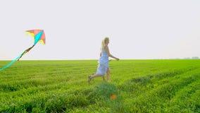 La madre joven del fin de semana de la familia con la hija del niño goza el correr con la cometa del vuelo se divierte en la natu metrajes
