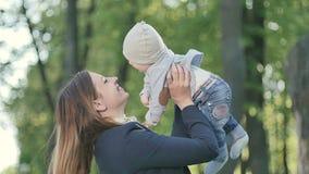 La madre joven disfruta con el pequeño hijo en parque metrajes