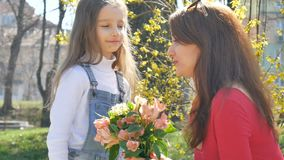 La madre joven en camisa roja está recibiendo un ramo de flores coloridas de su pequeña hija rubia y la está besando almacen de metraje de vídeo