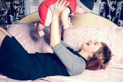 La madre joven es tenencia alegre al pequeño niño en sus brazos fotos de archivo libres de regalías