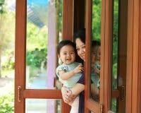 La madre joven está celebrando a su bebé que sonríe y que se coloca en la puerta de cristal Imagen de archivo