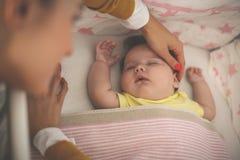 La madre joven está durmiendo su bebé imagenes de archivo