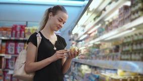 La madre joven está leyendo las inscripciones en una etiqueta de un tarro con puré del bebé en tienda almacen de metraje de vídeo