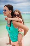La madre joven está montando a su hija querida en Imagen de archivo libre de regalías