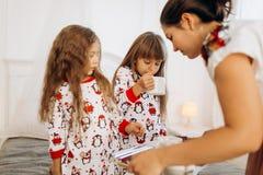 La madre joven está trayendo el cacao con las melcochas y las galletas a sus hijas en los pijamas que se sientan en la cama en e imagenes de archivo