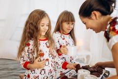 La madre joven está trayendo el cacao con las melcochas y las galletas a sus hijas en los pijamas que se sientan en la cama en e fotos de archivo