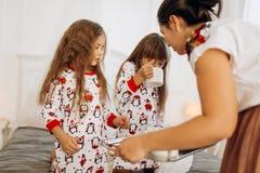 La madre joven está trayendo el cacao con las melcochas y las galletas a sus hijas en los pijamas que se sientan en la cama en e fotografía de archivo