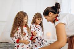 La madre joven está trayendo el cacao con las melcochas y las galletas a sus hijas en los pijamas que se sientan en la cama en e foto de archivo