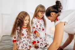 La madre joven está trayendo el cacao con las melcochas y las galletas a sus hijas en los pijamas que se sientan en el malo en e foto de archivo libre de regalías