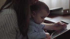 La madre joven est? trabajando en la tabla con las carpetas del ordenador port?til y de los documentos El peque?o beb? sienta rod almacen de metraje de vídeo