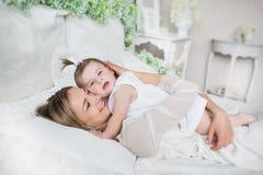 La madre joven feliz abraza a su pequeño bebé en una cama Fotografía de archivo libre de regalías