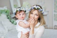 La madre joven feliz besa la mano de su pequeño niño en casa Fotos de archivo libres de regalías