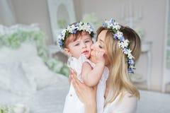 La madre joven feliz besa a su pequeño niño en casa Foto de archivo libre de regalías