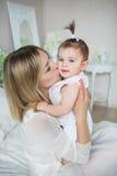 La madre joven feliz celebra en las manos y besa a su pequeño bebé Imagen de archivo