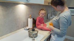 La madre joven feliz cocina con un niño que se siente en una cocina de la tabla en casa almacen de video