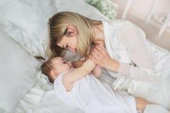 La madre joven feliz juega con su pequeño bebé en una cama Fotos de archivo libres de regalías