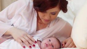 La madre joven frota ligeramente a su pequeño bebé lindo en la cama blanca almacen de video