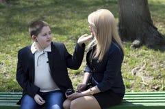 La madre joven habla con el niño, sentándose en un banco Imágenes de archivo libres de regalías