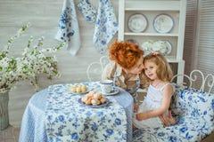 La madre joven habla con su hija en la cocina foto de archivo libre de regalías