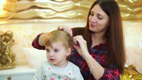 La madre joven hace el estilo de pelo para su hija del niño en el hogar adornado festivo metrajes