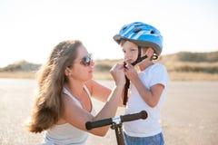 La madre joven hermosa ayuda a su pequeño hijo lindo puesto en casco del deporte Fotos de archivo