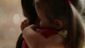 La madre joven hermosa con su hija está abrazando Se están divirtiendo mucho junto metrajes