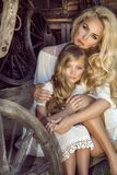 La madre joven hermosa con su hija se vistió en ropa de la primavera y guirnaldas de flores Foto de archivo