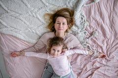 La madre joven hermosa y su pequeña hija están mintiendo juntas en la cama en el dormitorio, están jugando, están abrazando y se  imagen de archivo libre de regalías