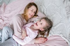 La madre joven hermosa y su pequeña hija están mintiendo juntas en la cama en el dormitorio, están riendo, están abrazando y se e imagen de archivo libre de regalías