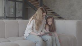 La madre joven hermosa y su pequeña hija linda están utilizando una tableta y una sonrisa, sentándose en el sofá en la casa grand almacen de metraje de vídeo