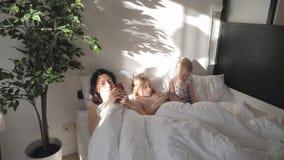 La madre joven, la hija y poco hijo est?n utilizando los artilugios que mienten en una cama blanca Familia moderna del concepto d metrajes
