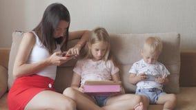 La madre joven, la hija y poco hijo est?n utilizando los artilugios que mienten en una cama blanca Familia moderna del concepto d almacen de metraje de vídeo