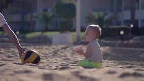 La madre joven juega con su bebé con la bola en la cámara lenta almacen de metraje de vídeo