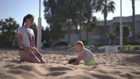 La madre joven juega con su beb? con la bola en la c?mara lenta metrajes