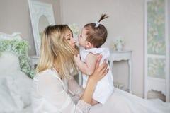 La madre joven juega el wirh su pequeño bebé en una cama en casa Imagen de archivo libre de regalías
