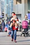 La madre joven lleva a su bebé en el paso de cebra, Shangai, China Imagen de archivo libre de regalías