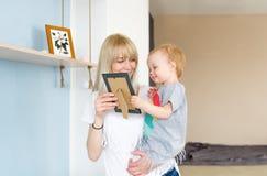 La madre joven mira el marco de la foto con el niño del bebé Fotos de archivo