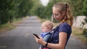 La madre joven moderna con un niño utiliza un teléfono móvil metrajes