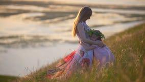 La madre joven pone la guirnalda en la cabeza de su hija que abrace a la mamá en el prado del verano en la puesta del sol almacen de metraje de vídeo