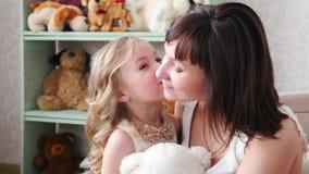 La madre joven que se divierte con su hija, besos de la hija, abraza a la madre almacen de video