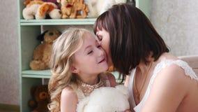 La madre joven que se divierte con su hija, mamá besa a su hija almacen de video