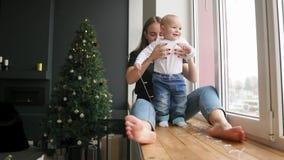 La madre joven se está sentando con su hijo en el travesaño de la ventana adornado con la guirnalda de la Navidad y está mirando  almacen de metraje de vídeo