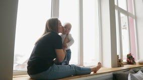 La madre joven se está sentando con su hijo en el travesaño de la ventana adornado con la guirnalda de la Navidad y está mirando  almacen de video