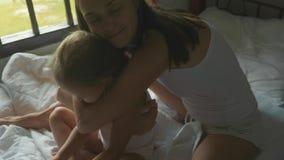 La madre joven se sienta en la cama y peinar a su hija en la cámara lenta almacen de video