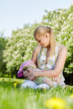 La madre joven se sienta en parque y celebra a la bebé-muchacha durmiente Fotos de archivo